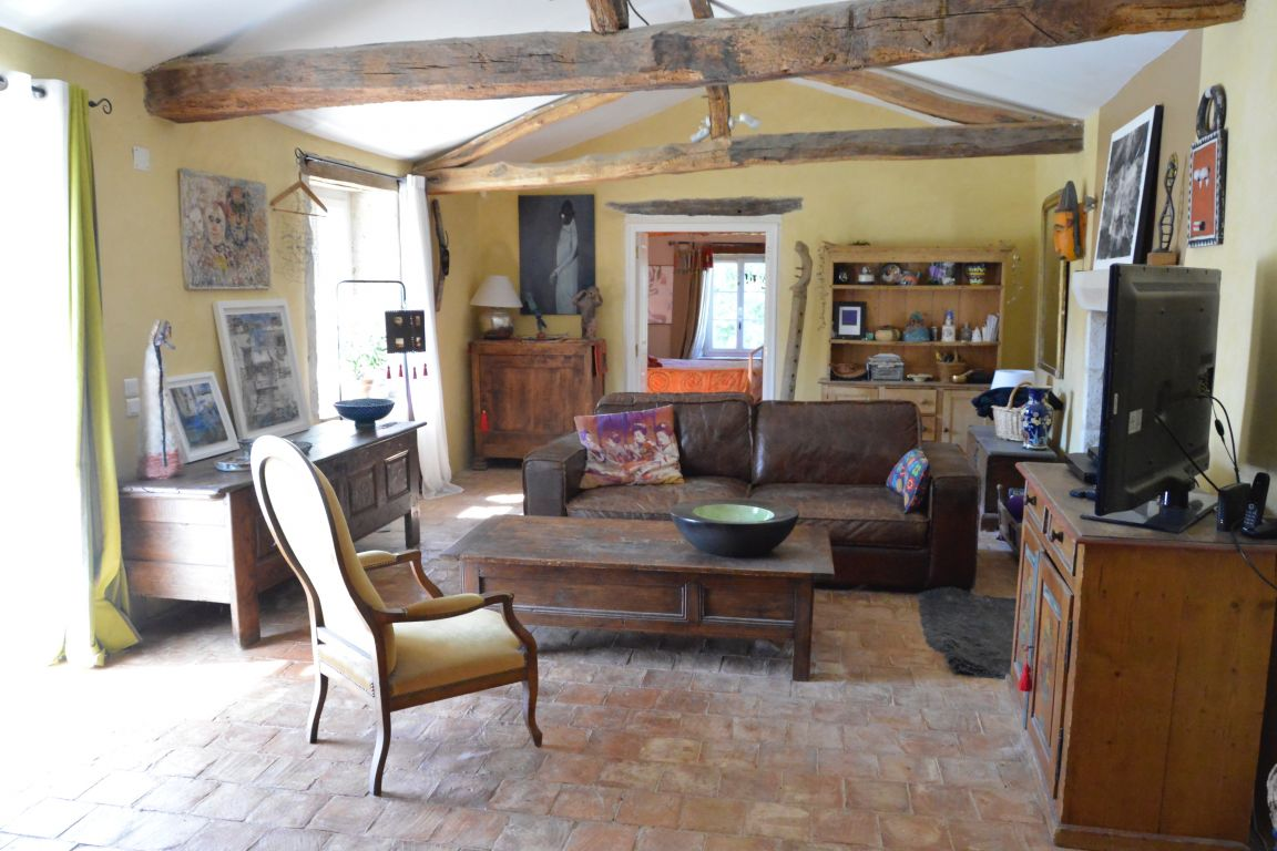 Charming stone-built farmhouse (of 200m2 approx), sympathetically renovated retaining it's authenticity. With 12.5 acres of land and woods.